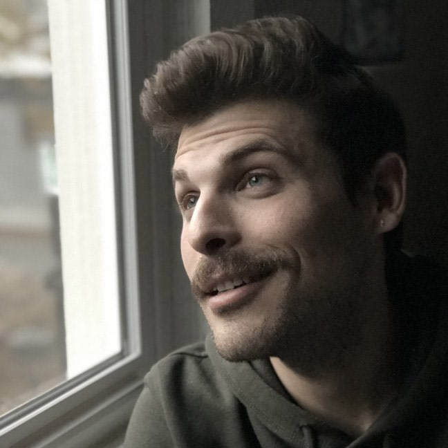 Headshot of Andrew Tolman looking out of a window.